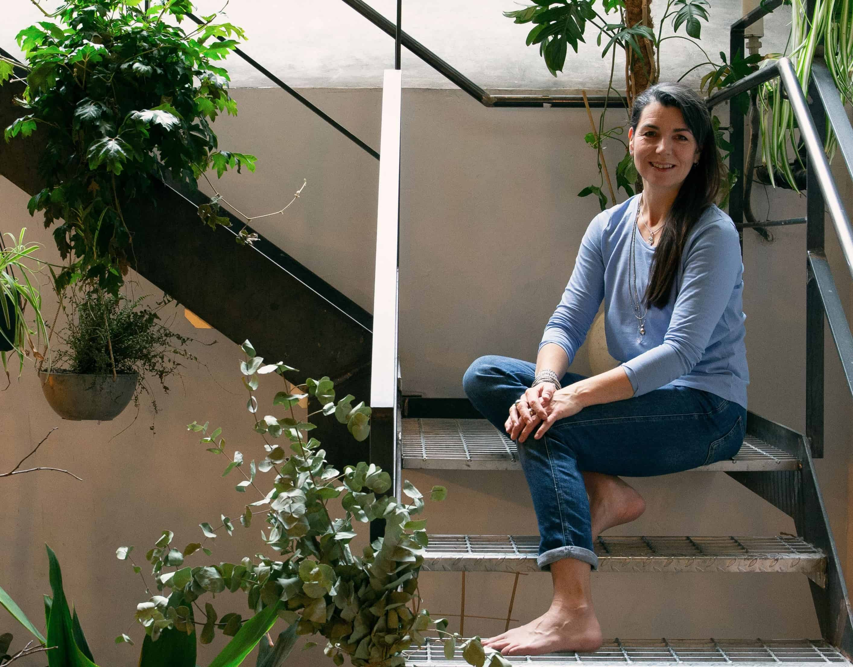 Deborah sitting on stairs with plants